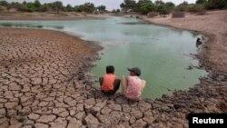 Trẻ em Ấn Độ ngồi trên bờ ao bị khô hạn một phần trong bang Gujarat