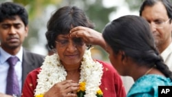 A Sri Lankan ethnic Tamil girl applies vermillion on the forehead of U.N. High Commissioner for Human Rights Navi Pillay. File
