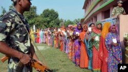 Indian security personnel guard as women voters stand in a queue to cast their votes at a polling station during the first of the five phase voting for state legislative assembly at Mahmoodpur village, in Samastipur district of India's eastern state Bihar, Oct. 12, 2015.