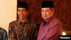 "FILE - Indonesian President Susilo Bambang Yudhoyono shakes hand with Joko ""Jokowi"" Widodo during a meeting at the presidential palace in Jakarta, July 20, 2014."