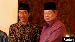 "FILE - Indonesian President Susilo Bambang Yudhoyono (r) shakes hand with presidential candidate Joko ""Jokowi"" Widodo during a meeting at the presidential palace in Jakarta."