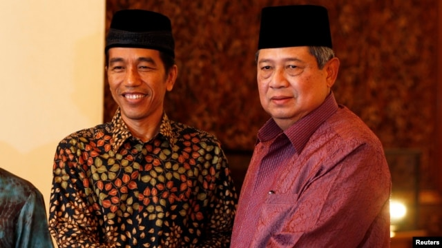 """FILE - Indonesian President Susilo Bambang Yudhoyono shakes hand with Joko """"Jokowi"""" Widodo during a meeting at the presidential palace in Jakarta, July 20, 2014."""