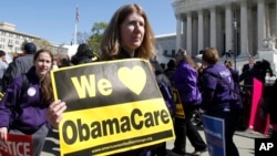 "Holding a sign saying ""We Love ObamaCare"" supporters of health care reform rally in front of the Supreme Court in Washington, Mar. 27, 2012."