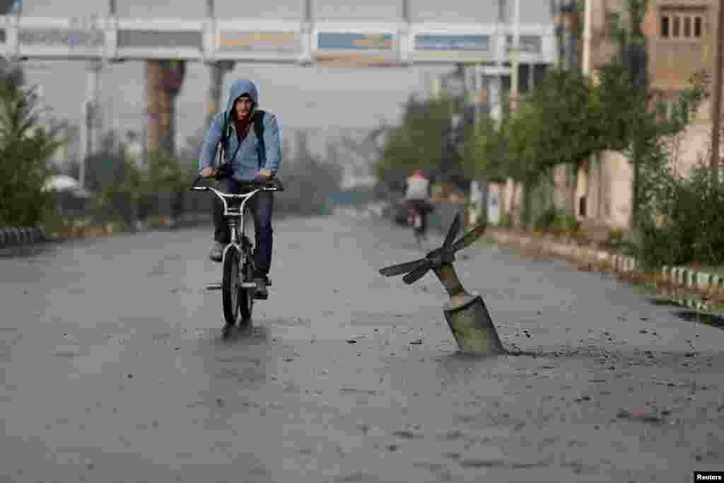 បុរសមួយរូបជិះកង់ជិតអ្វីដែលក្រុមសកម្មជននិយាយថា ជាសំបកគ្រាប់បែកចង្កោមដែលបានផ្ទុះហើយ នៅក្រុង Douma ភាគខាងកើតតំបន់ Ghouta ក្នុងរដ្ឋធានីដាម៉ាស ប្រទេសស៊ីរី។