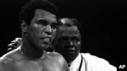 FILE - Muhammad Ali stands with longtime trainer Bundini Brown after Ali became the first man to win the world heavyweight championship three times at the Superdome in New Orleans, September 15, 1978.