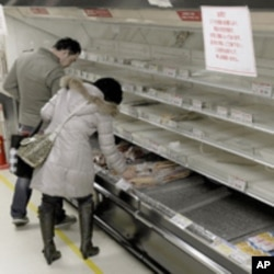 People shop for food from an almost empty shelf at a Tokyo store, March 15, 2011.