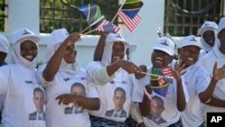 Des Tanzaniens applaudissant au passage du président Obama