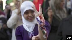 一名利比亚女孩在班加西打出胜利手势,她的胳膊上涂着法美英意和卡塔尔国旗