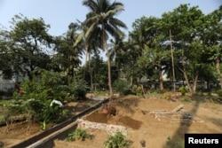 Seorang asisten Sayyed Munir Kamruddin, seorang penggali kubur, menyiapkan kuburan untuk penguburan korban COVID-19 di sebuah pemakaman di Mumbai, India 28 April 2021. (REUTERS / Francis Mascarenhas)