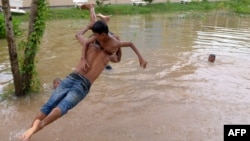 A Cambodian man carries a boy as he leaps into flood waters on the outskirts of Phnom Penh on September 27, 2013.