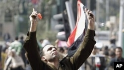 A man identified only as Fathi, wearing the uniform of a captain in the Egyptian army, is carried by demonstrators on Tahrir, or Liberation Square, in Cairo, Egypt, Monday Jan. 31, 2011