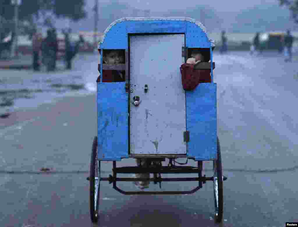 Schoolchildren travel to their school in a rickshaw on a cold morning in the old quarter of Delhi, India.