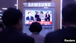 People watch a TV news report about the meeting between North Korean leader Kim Jong Un and Chinese President Xi Jinping at a railway station in Seoul, South Korea May 8, 2018. REUTERS/Kwak Sung-Kyung