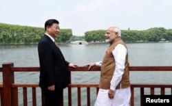 2018年4月28日,中国国家主席习近平和印度总理纳伦德拉·莫迪在中国武汉沿东湖漫步时交谈(印度新闻局通过路透社发布的照片)。