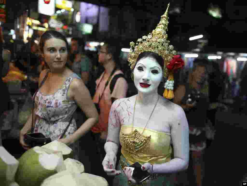 Seorang turis memperhatikan seorang perempuanThailand berpakaian dalam kostum hantu untuk acaraHalloween membeli kelapa diBangkok, Thailand.