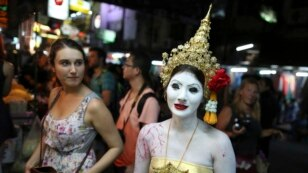 A tourist looks at a Thai woman dressed in a ghost costume for Halloween buying coconut in Bangkok, Thailand.