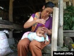 Seorang ibu di Turi, Sleman, Yogyakarta mencukur kepala anaknya di kandang kambing. (Foto:VOA/ Nurhadi)
