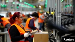 Employees handle packages in the new Amazon logistics center in Dortmund, Germany, Nov. 14, 2017.
