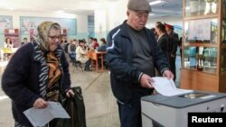 People vote at a polling station during the presidential election in Bishkek, Kyrgyzstan, Oct. 15, 2017.