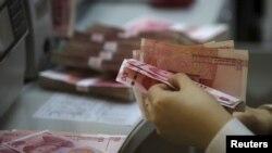 中国北京工商银行的一名店员点数百元人民币(2016年4月13日)