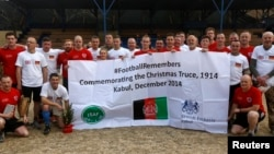 German and British troops pose for a photo after a football match to commemorating the Christmas Truce of 1914, at the ISAF Headquarters in Kabul, Dec. 24, 2014.