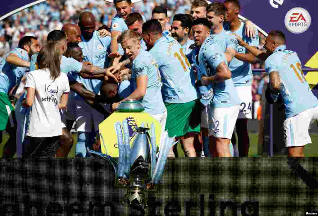 Manchester City's Oleksandr Zinchenko reacts as the trophy falls to the floor as players and staff celebrate winning the premier league title at the Etihad Stadium in Manchester,  Britain, May 6, 2018.