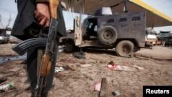 Seorang petugas keamanan berdiri di dekat kendaraan yang hancur akibat ledakan bom bunuh diri di dekat Peshawar (14/3). Sedikitnya tujuh orang dilaporkan tewas dan 35 lainnya terluka dalam serangan yang menarget panser militer ini.
