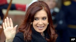 Argentina's President Cristina Fernandez waves to photographers in Montevideo, Uruguay July 12, 2013.