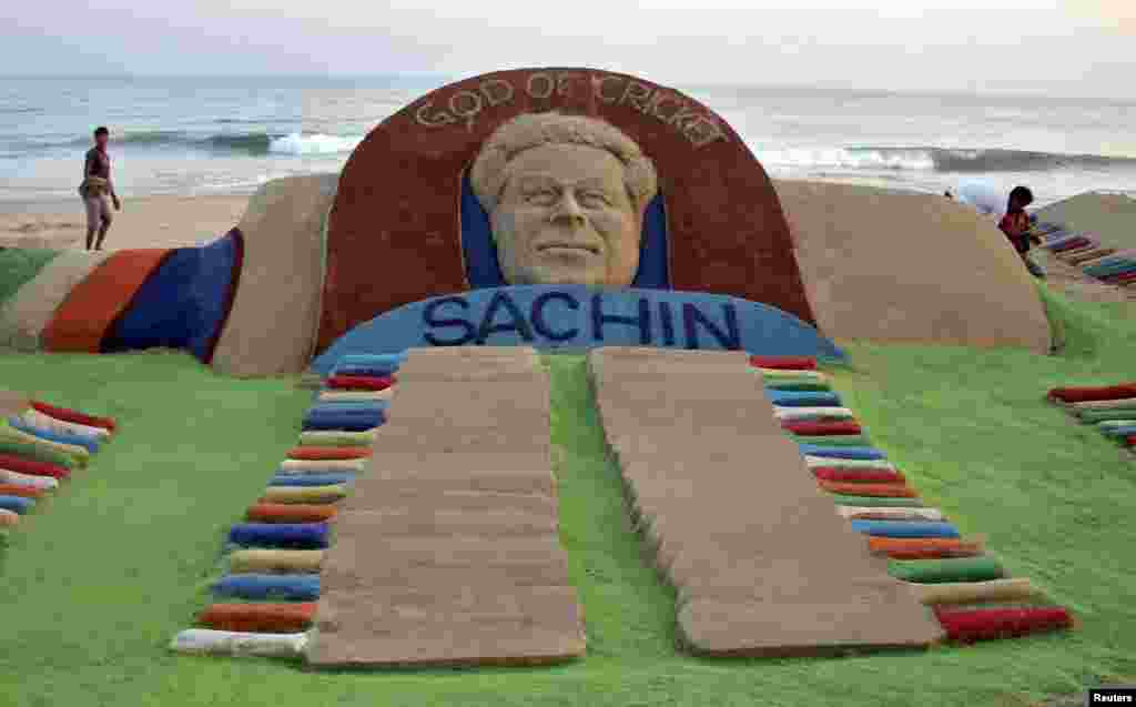 People walk past a sand sculpture of cricketer Sachin Tendulkar created by Indian sand artist Sudarshan Patnaik, in the eastern Indian state of Odisha, Nov. 13, 2013.