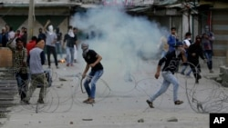 Kashmiri protesters shout slogans as a tear gas shell explodes near them in Srinagar, Indian-controlled Kashmir, May 12, 2017. Government forces used tear gas smoke and rubber bullets to disperse dozens of rock-throwing protesters demonstrating against Indian rule in Kashmir Friday.