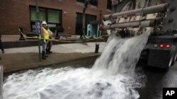受到桑迪颶風襲擊的紐約市砲台公園附近的辦公樓﹐抽水機把水從被淹的地下室中抽上來。