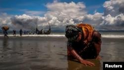 Seorang pengungsi Rohingya menyentuh pasir di pantai Bengal, Shah Porir Dwip, Bangladesh, 11 September 2017, setibanya di kawasan itu. (Foto: dok). Militer Malaysia mengukuhkan pihaknya menghalau sedikitnya satu perahu mencurigakan yang penuh berisi orang Rohingya, Jumat (17/4).