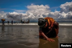 FILE - An exhausted Rohingya refugee woman touches the shore after crossing the Bangladesh-Myanmar border by boat through the Bay of Bengal, in Shah Porir Dwip, Bangladesh, Sept. 11, 2017.
