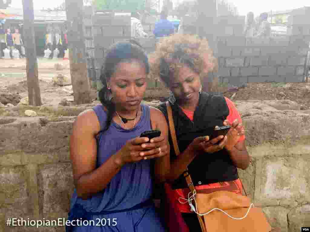 Duas jovens conferem as notícias sobres as eleições nos seus telemóveis