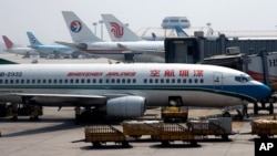 Airport worker unloads passenger luggage into a Shenzhen Airliner parked at the Beijing International Aiport in Beijing, China, Aug. 15, 2007.