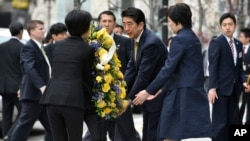 Japanese Prime Minister Shinzo Abe, center right, and his wife Akie, second from right, join aides in placing a wreath at the site of one of the 2013 Boston Marathon bombings Monday, April 27, 2015, in Boston. (AP Photo/Josh Reynolds)