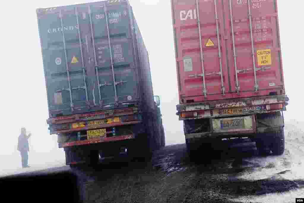 راننده کامیون های ایرانی پیش از عبور از گذرگاه یک هزار و هشتصد متری ارمنستان برای اطمینان از چرخ های زمستانی توقف می کنند. ( گذرگاه توخ مانوک، ٢١ فوریه سال ٢٠١٣) (وی اوندریتز / صدای آمریکا)