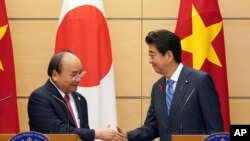 Thủ Tướng Nhật Shinzo Abe (phải) và Thủ Tướng VN Nguyễn Xuân Phúc bắt tay sau cuộc họp báo chung tại văn phòng Thủ Tướng Abe ở Tokyo hôm 8/10/2018. (AP Photo/Eugene Hoshiko, Pool)