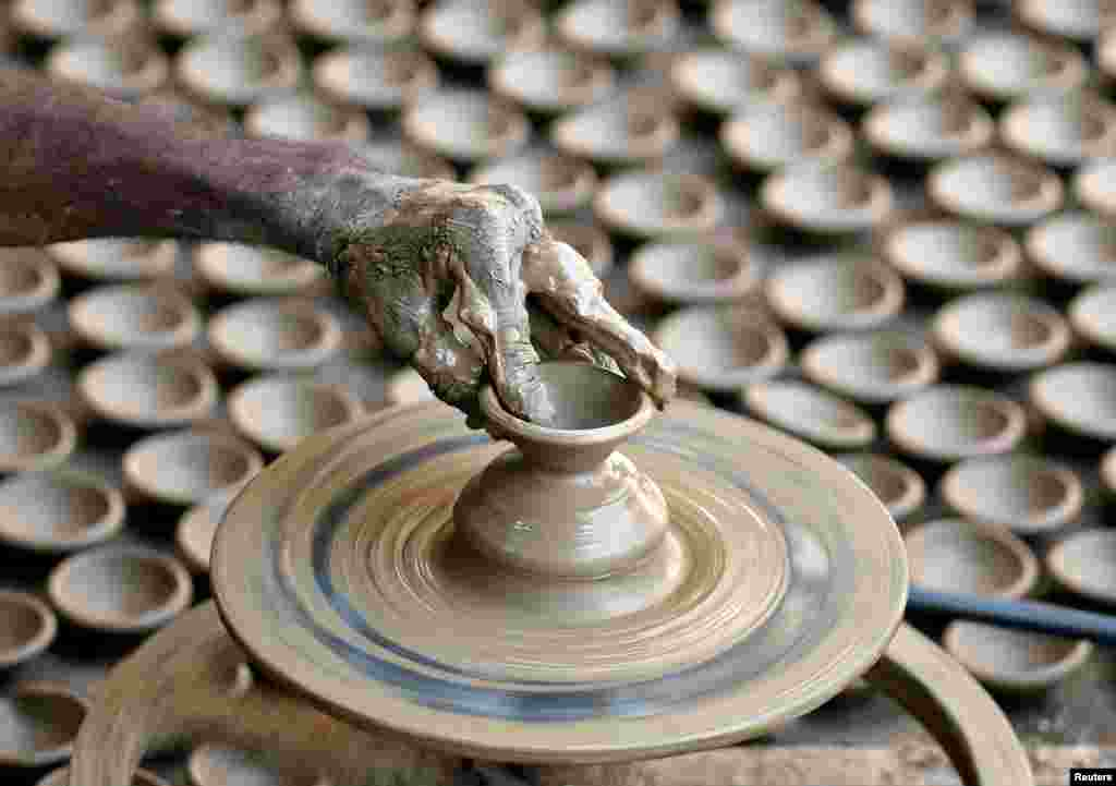 A man makes earthen lamps for Diwali, the Hindu festival of lights, at a workshop in Ahmedabad, India.