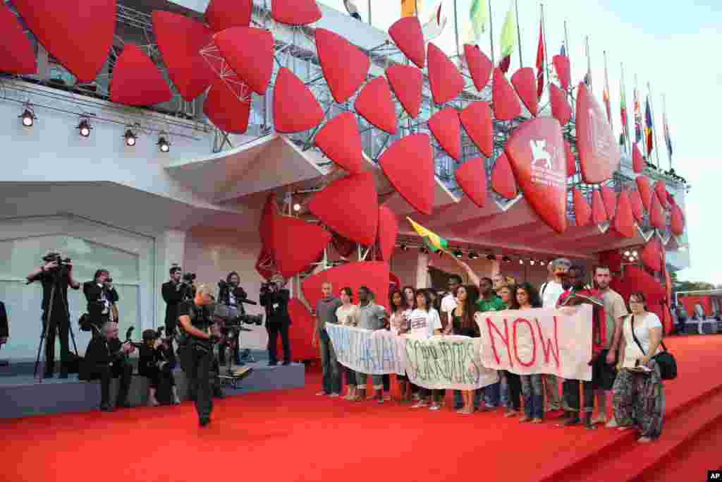 Barefoot marches in support of migrants took place in cities across Italy on Friday.  This group reached the red carpet of the Venice Film Festival.