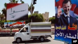 FILE - A vehicle drives past campaign posters for a presidential election in Damascus, Syria, May 12, 2014. Opposition politicians argue upcoming parliamentary elections are an effort by Assad to project a political legitimacy he doesn't have.
