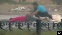 图为8月4日一名抗议者蹲在伤者旁边