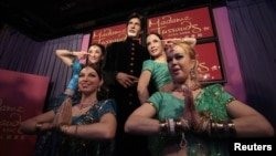 Models pose next to a wax figure of Bollywood icon Amitabh Bachchan.