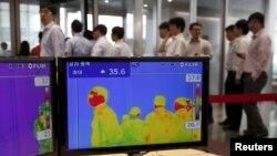 2015年6月9日在韩国位于首尔市中心,员工走过办公楼的热成像仪。