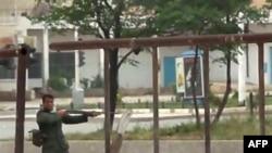 Bức ảnh lấy từ một video cho thấy một binh sĩ Syria đang chĩa súng vào người biểu tình