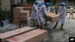 Jammu and Kashmir State Disaster Response Force soldiers carry empty coffins for transporting bodies of people who died of COVID-19 outside government medical hospital in Jammu, India, Wednesday, May 19, 2021. (AP Photo/Channi Anand)
