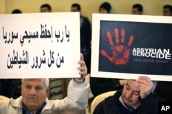 FILE - Assyrians citizens hold placards during a sit-in for abducted Christians in Syria and Iraq, at a church in Sabtiyesh area east Beirut, Lebanon, Feb. 26, 2015.