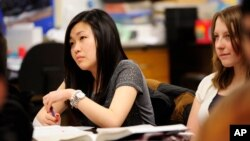 FILE - Sally Kim takes notes during a physics class at Columbia Independent School in Columbia, Mo., Feb. 27, 2012. Kim's parents, who live in South Korea, sent her to live with relatives in Columbia for a better education that provides more collegiate op
