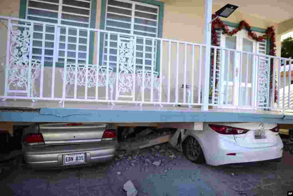 Unos automóviles aparecen aplastados debajo de una casa que se derrumbó después de un terremoto en Guánica, Puerto Rico, el lunes 6 de enero de 2020.