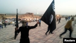 FILE - A fighter of the Islamic State holds up an IS flag and a weapon on a street in Mosul, Iraq.